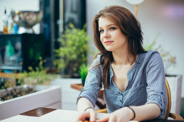 Ritratto di una giovane donna bella in un caffè. Foto Premium