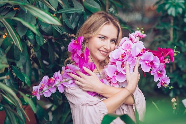 Ritratto di una giovane donna bionda che abbraccia i rami di fiori di orchidea Foto Gratuite