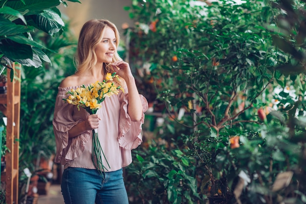 Ritratto di una giovane donna bionda sorridente che tiene distogliere lo sguardo del fiore giallo Foto Gratuite