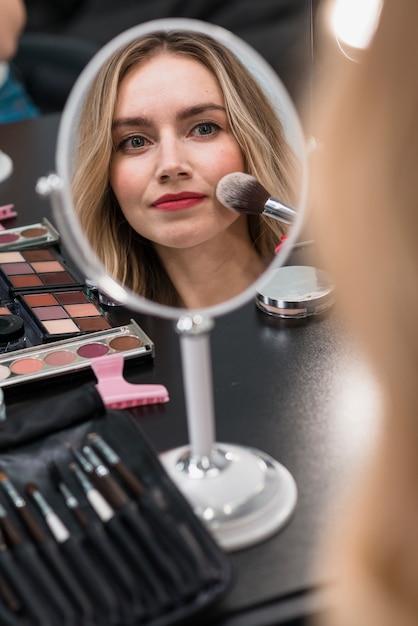 Ritratto di una giovane donna bionda utilizzando cosmetici Foto Gratuite