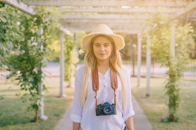 Ritratto di una giovane donna che indossa la fotocamera intorno al collo in piedi nel giardino Foto Gratuite