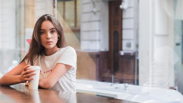 Ritratto di una giovane donna che si siede in caffè con la tazza di caffè da asporto in mano che guarda l'obbiettivo Foto Gratuite