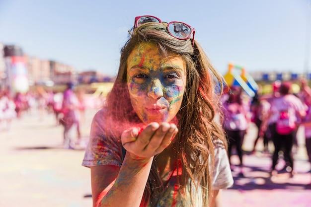 Ritratto di una giovane donna che soffia colore holi davanti alla telecamera Foto Gratuite