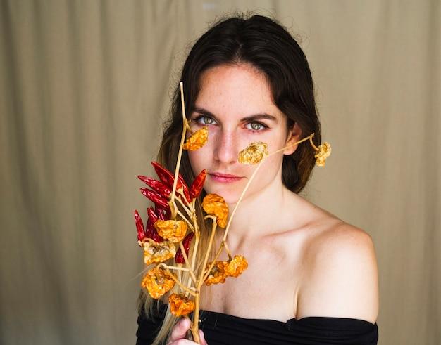 Ritratto di una giovane donna che tiene i peperoncini rossi Foto Gratuite