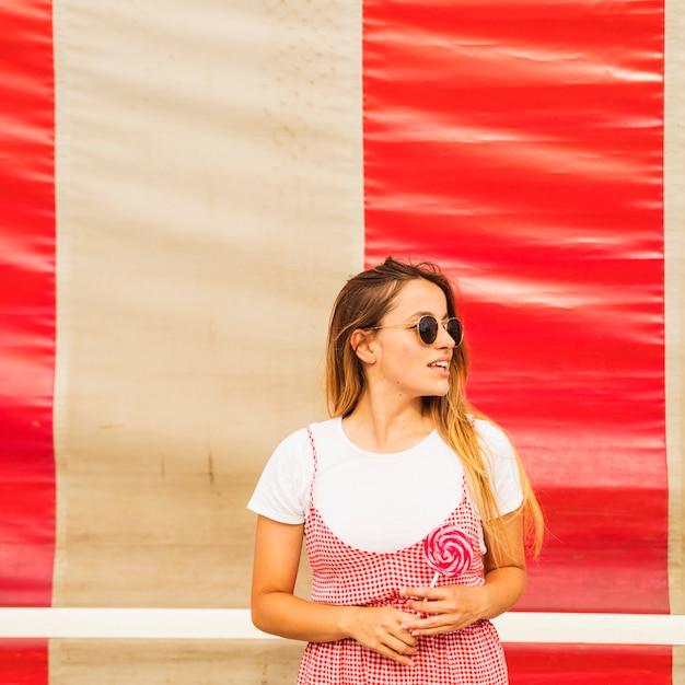 Ritratto di una giovane donna che tiene in mano il lecca-lecca rosso in cerca di distanza Foto Gratuite