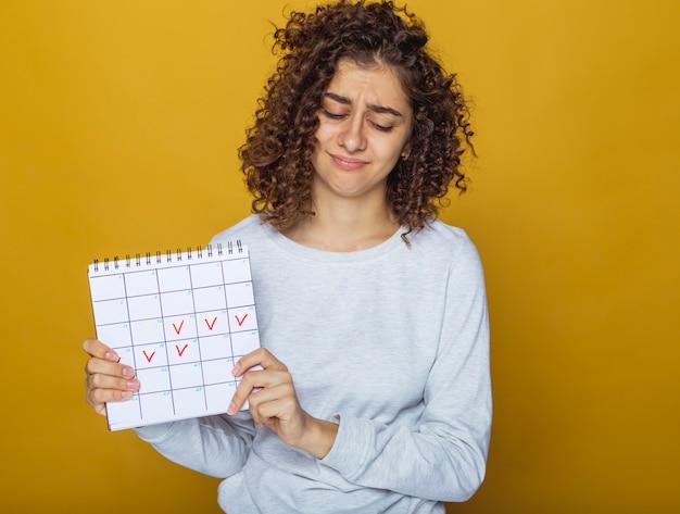 Ritratto di una giovane donna che tiene un calendario con i giorni contrassegnati Foto Premium