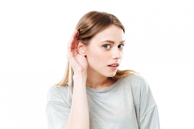 Ritratto di una giovane donna curiosa che prova a sentire voci Foto Gratuite