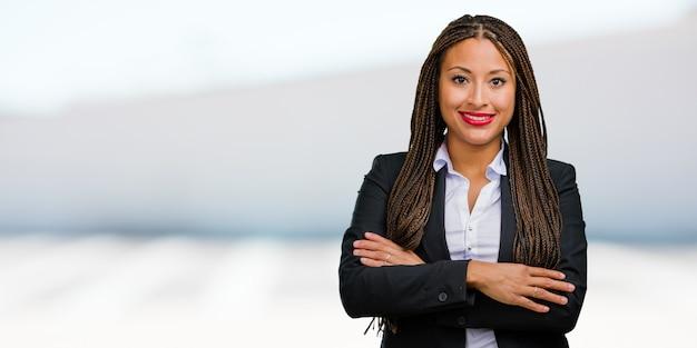 Ritratto di una giovane donna d'affari nero attraversando le braccia, sorridendo e felice, essendo fiducioso e amichevole Foto Premium