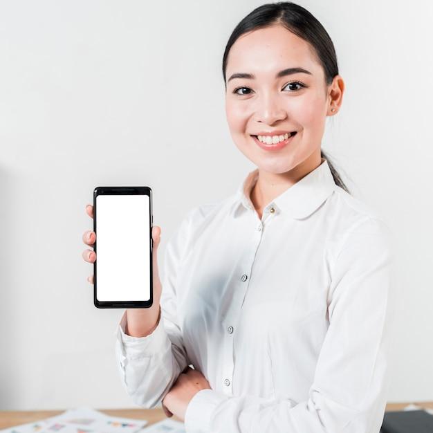 Ritratto di una giovane donna di affari asiatica sorridente che mostra il telefono cellulare dello schermo in bianco Foto Gratuite