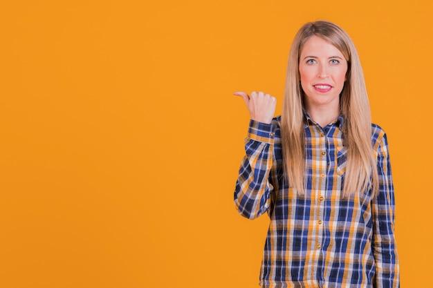 Ritratto di una giovane donna felice che mostra gesto del pollice contro uno sfondo arancione Foto Gratuite