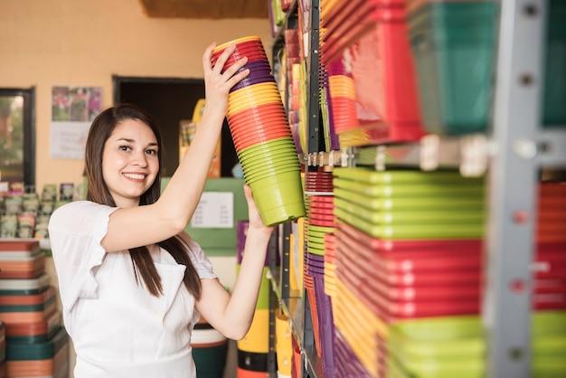 Ritratto di una giovane donna felice che organizza piante in vaso colorate in mensola Foto Gratuite