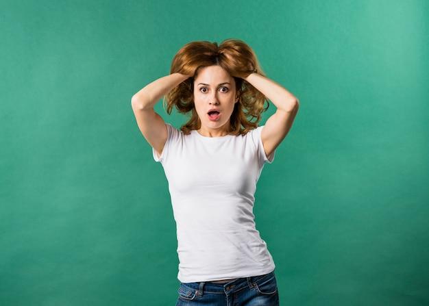 Ritratto di una giovane donna scioccata con le mani nei capelli su sfondo verde Foto Gratuite
