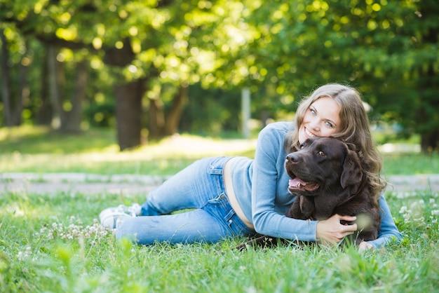 Ritratto di una giovane donna sorridente che ama il suo cane in giardino Foto Gratuite