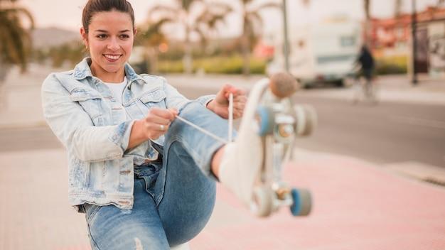 Ritratto di una giovane donna sorridente che lega il pizzo bianco del pattino del rullo sulla via Foto Gratuite