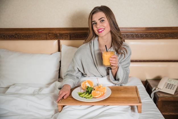 Ritratto di una giovane donna sorridente con frutta sana e un succo d'arancia nel letto Foto Gratuite
