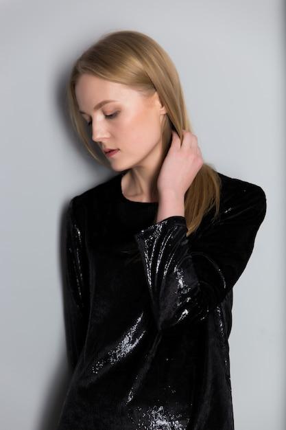 Ritratto di una giovane e bella donna bionda con trucco sera in un abito nero lucido vicino a un muro grigio Foto Premium