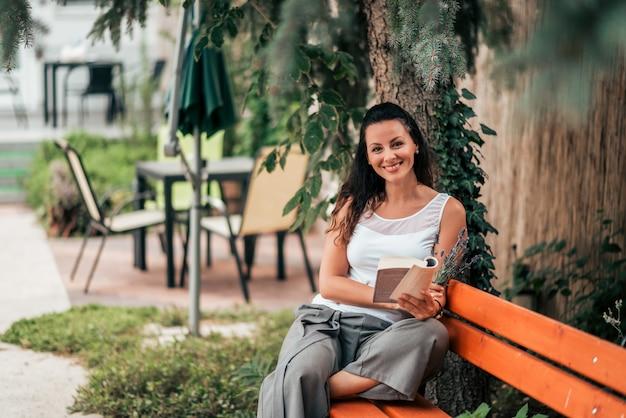Ritratto di una giovane e bella donna con un libro all'aperto. Foto Premium