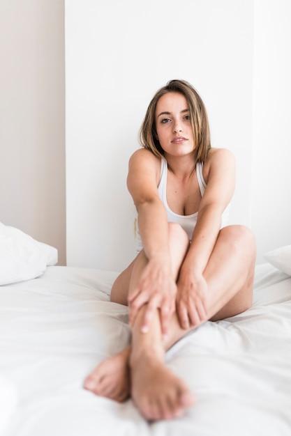 Ritratto di una giovane e bella donna seduta sul letto Foto Gratuite