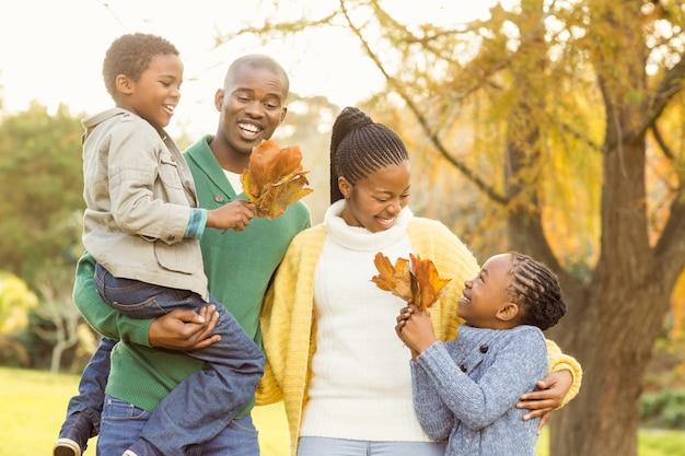 Ritratto di una giovane famiglia sorridente che tiene foglie Foto Premium