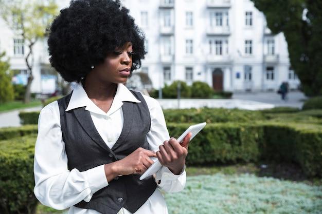Ritratto di una giovane imprenditrice africana fiduciosa guardando la tavoletta digitale Foto Gratuite