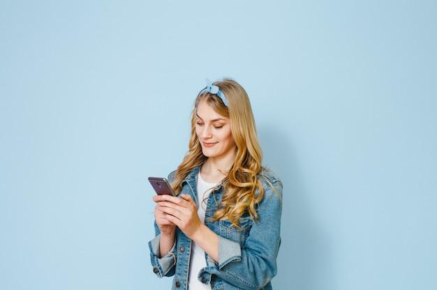 Ritratto di una giovane ragazza bionda felice perché vede nel suo telefono cellulare isolato su sfondo blu Foto Premium