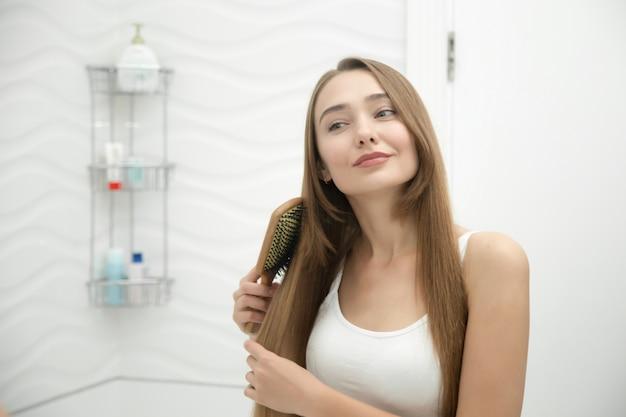 Ritratto di una giovane ragazza sorridente spazzolare i capelli Foto Gratuite