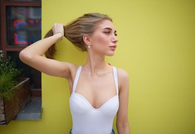 Ritratto di una giovane ragazza su uno sfondo giallo Foto Premium