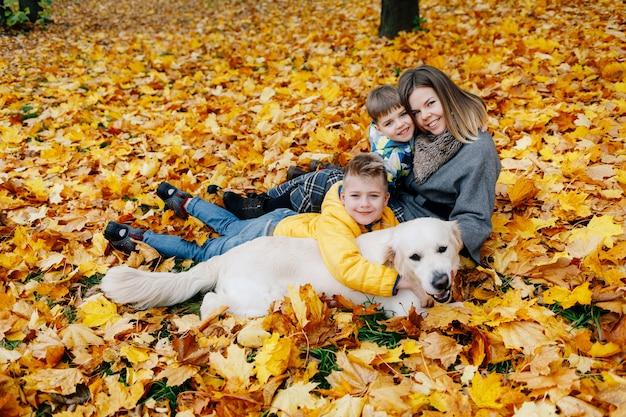 Ritratto di una madre con due figli e un cane in un parco in autunno Foto Premium