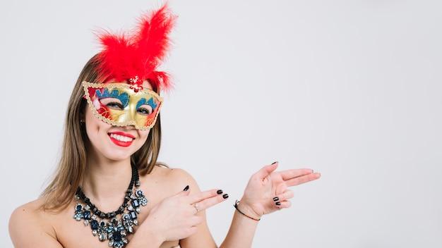 Ritratto di una maschera d'uso sorridente di carnevale della donna che gesturing sul fondo bianco Foto Gratuite