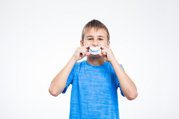 Ritratto di una muffa dell'intonaco dei denti della tenuta del ragazzo contro fondo bianco Foto Gratuite