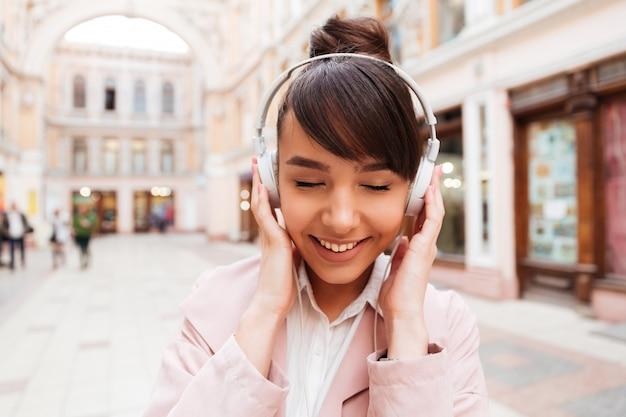 Ritratto di una musica d'ascolto sorridente della giovane donna sveglia con le cuffie Foto Gratuite