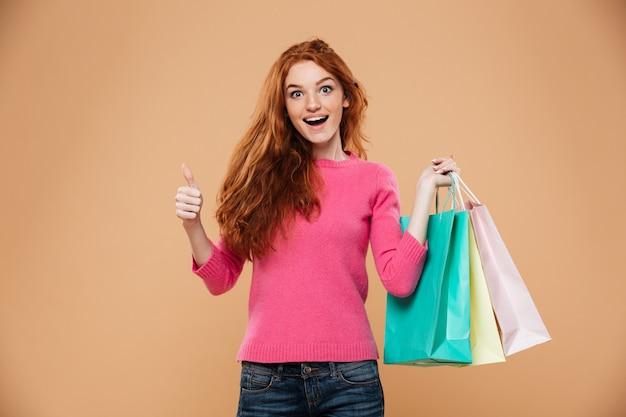 Ritratto di una ragazza allegra attraente rossa con borse della spesa Foto Gratuite