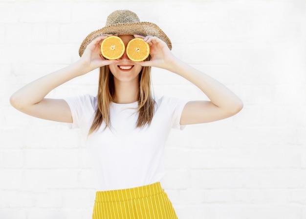 Ritratto di una ragazza allegra che tiene due fette di un'arancia al suo fronte sopra la parete bianca Foto Premium