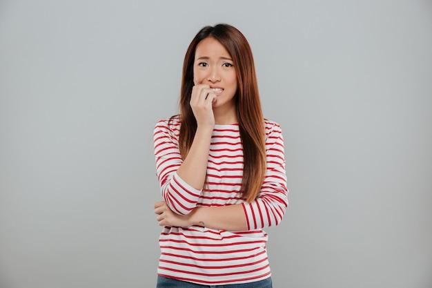 Ritratto di una ragazza asiatica nervosa che morde le sue unghie Foto Gratuite