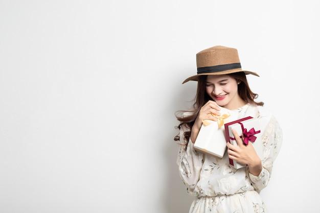 Ritratto di una ragazza asiatica sorridente felice in vestito che tiene la scatola attuale, bella ragazza tailandese con il contenitore di regalo. Foto Premium
