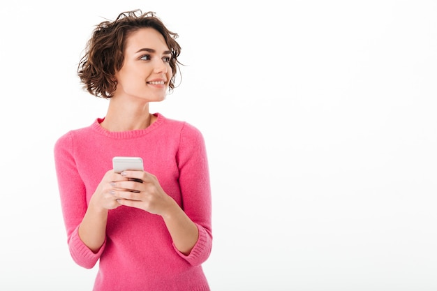 Ritratto di una ragazza attraente sorridente che tiene telefono cellulare Foto Gratuite