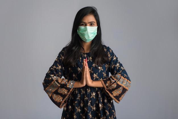 Ritratto di una ragazza che indossa una mascherina medica che fa saluto con il gesto di namaste. Foto Premium