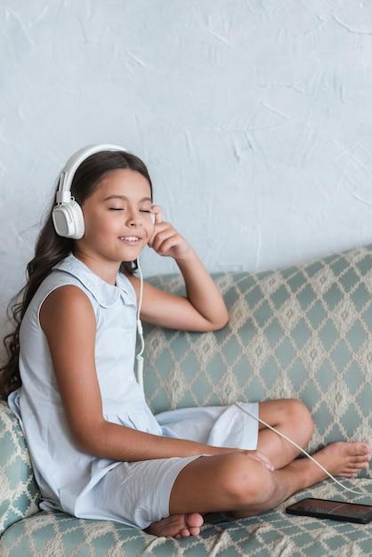 Ritratto di una ragazza che si siede sul sofà che gode della musica sulla cuffia allegata al telefono cellulare Foto Gratuite