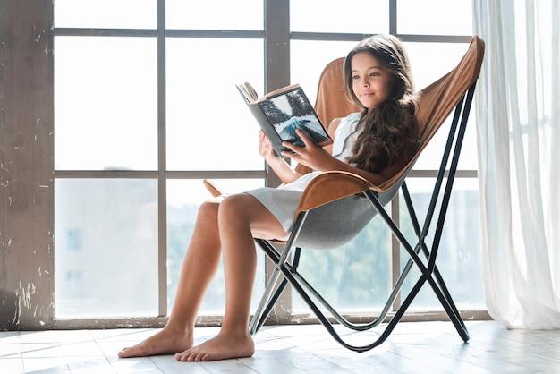 Ritratto di una ragazza che si siede sulla sedia vicino al libro di lettura della finestra Foto Gratuite