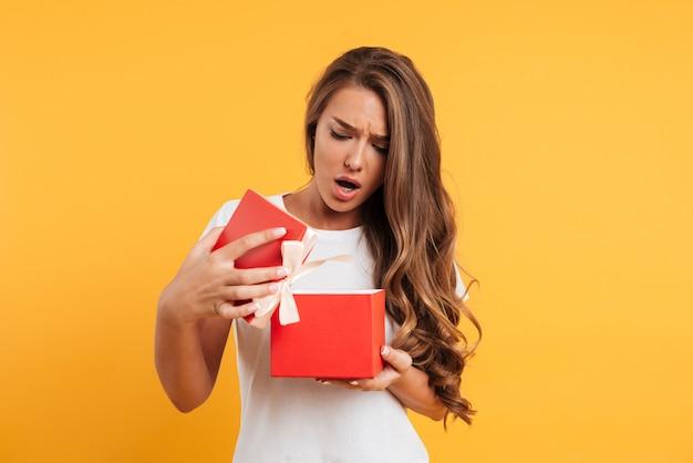 Ritratto di una ragazza delusa sconvolto apertura confezione regalo Foto Gratuite
