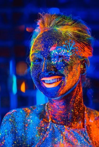 Ritratto di una ragazza dipinta in polvere fluorescente. Foto Premium