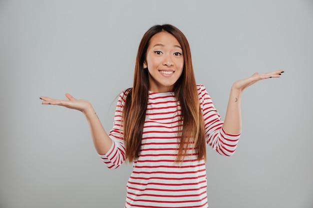 Ritratto di una ragazza divertente confusa che scrolla le spalle le spalle Foto Gratuite