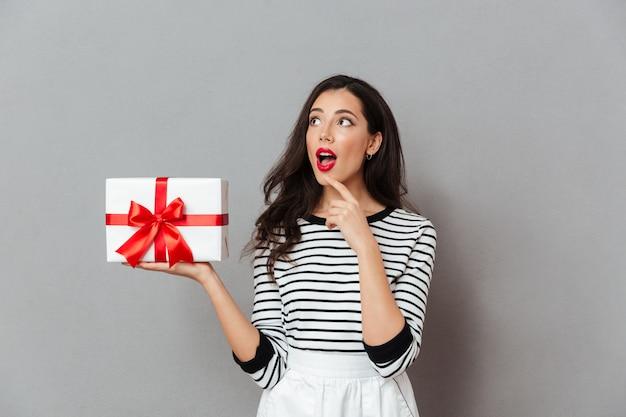 Ritratto di una ragazza emozionante che tiene casella attuale Foto Gratuite