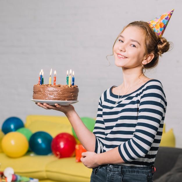 Ritratto di una ragazza felice che tiene torta deliziosa sul piatto bianco nella festa Foto Gratuite