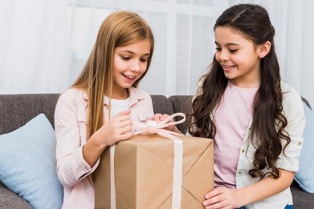 Ritratto di una ragazza guardando il suo amico sorridente che apre il contenitore di regalo Foto Gratuite