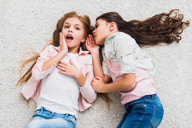 Ritratto di una ragazza pettegolezzo che dice un segreto nell'orecchio alla sua amica sdraiata sul tappeto Foto Gratuite