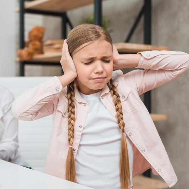 Ritratto di una ragazza sconvolta che copre le orecchie con due mani Foto Gratuite