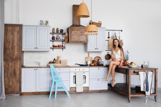 Ritratto di una ragazza seduta sul tavolo della cucina accanto alla stufa, cucina salsa in padella Foto Premium