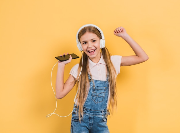Ritratto di una ragazza sorridente che gode della musica sulla cuffia attraverso il dancing del telefono cellulare contro fondo giallo Foto Gratuite