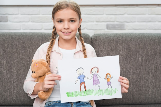 Ritratto di una ragazza sorridente che si siede sul divano che mostra la sua famiglia disegno su carta Foto Gratuite